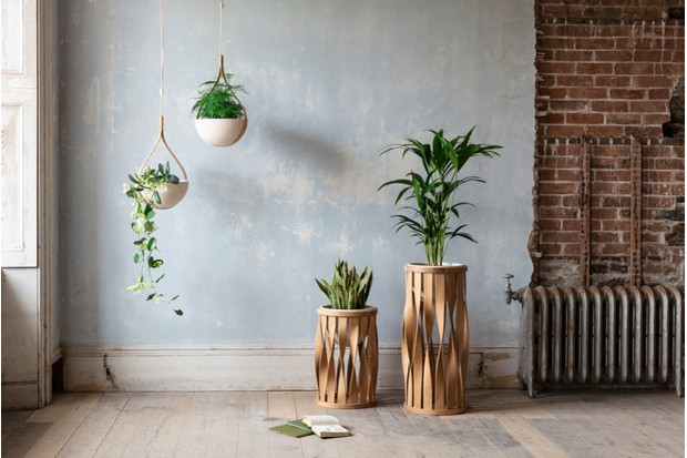 Tom's Merryn floor standing planter (from £695) filled with leafy plants in front of an exposed brick wall.