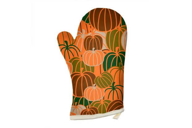 A single oven glove printed with a collage of orange pumpkins