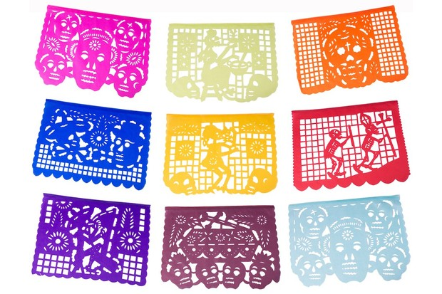 Traditional Day of the Dead paper flags in bright, primary colours. Each flag features laser-cut skulls and characters.