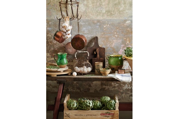 A rustic table topped with confit pots, Confit pots in bright green or yellow glazes, linen tablecloths, plenty of rustic wooden boards and strings of garlic