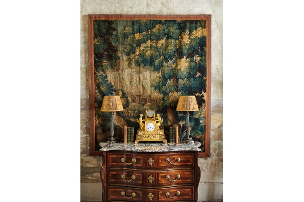 A curved antique commode decorated with an old ormolu clock flanked with table lamps. A large-scale green and brown tapestry hangs behind.
