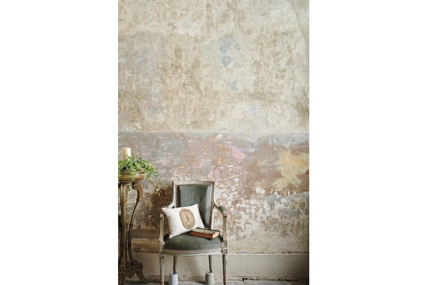 An antique Louis XVI chair in front of a stripped, bare-plaster wall.