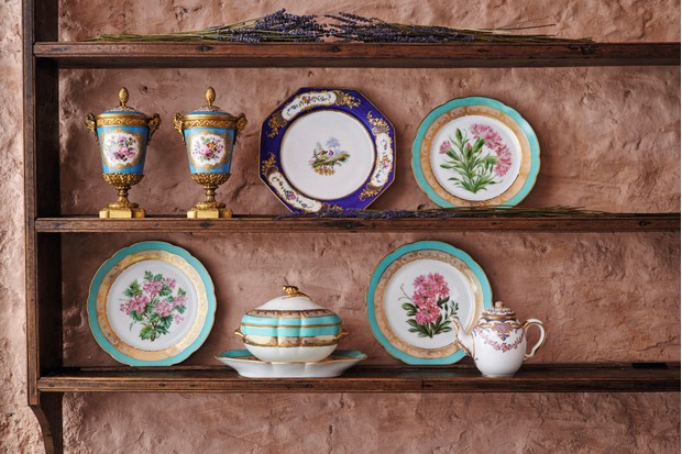 An array of colourful Sevres ceramics displayed on the open shelves of a dresser.