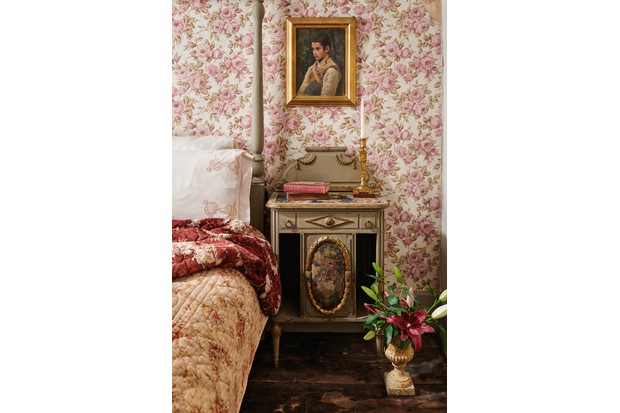 An antique four poster bed against bold floral wallpaper and a gold bedside table.