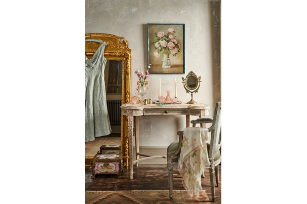 A romantic dressing table topped with pink glassware and a gilt hand mirror.