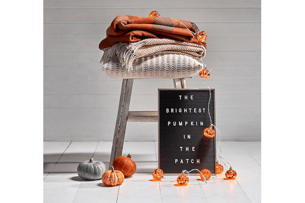 A string of illuminated pumpkin fairy lights alongside a washed wooden stool, woollen orange blankets and a vintage-style letter board.