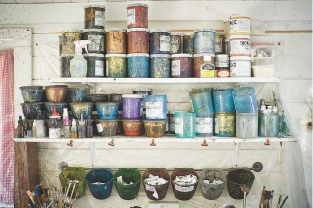 The shelves of Jemma's studio piled high with pots of paint and dye