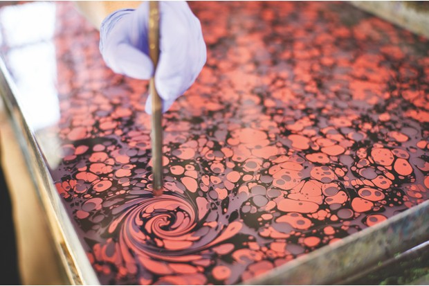 Jemma uses a stylus to swirl ink floating atop a tray of water