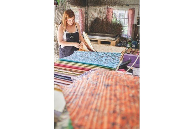 Jemma in her back garden workshop, surrounded by piles of richly marbled papers