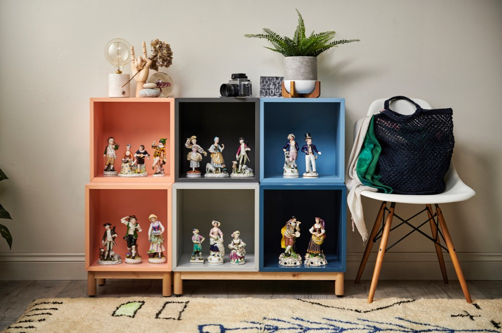 Small figurines on colourful shelves next to a white chair