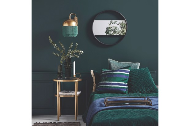 Freema fringed wall lamp in Gold and Green, £155; Reidun round frame crossbar wall mirror, £180, both Out There Interiors. In a bedroom setting with emerald green bedding and walls with gold details