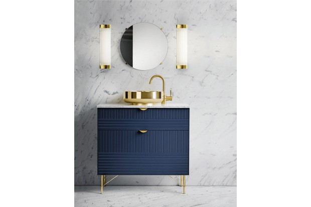 Davey Lighting Pillar wall lights, from £419, Original BTC. Set in a bathroom with marbled walls, brass sink and taps and blue cabinet