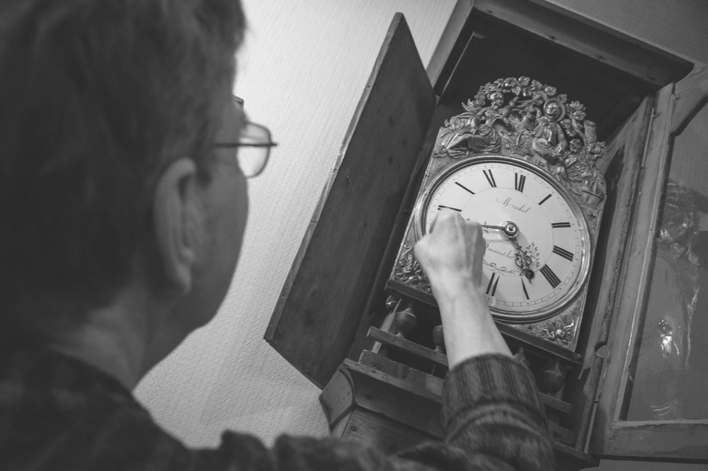 Man cleaning an antique longcase clock