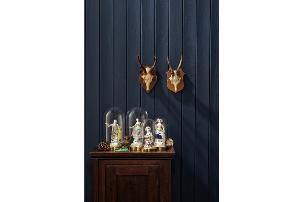 Figurines displayed in glass domes against a Farrow & Ball painted wall and antique mounted antlers