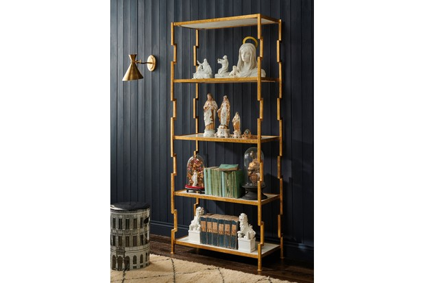 Antique and vintage figures displayed on a gold shelf next to a printed stool with antique books, brass wall light and display domes