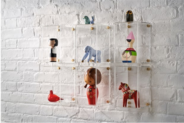 Vintage objects displayed in clear wall-mounted boxes