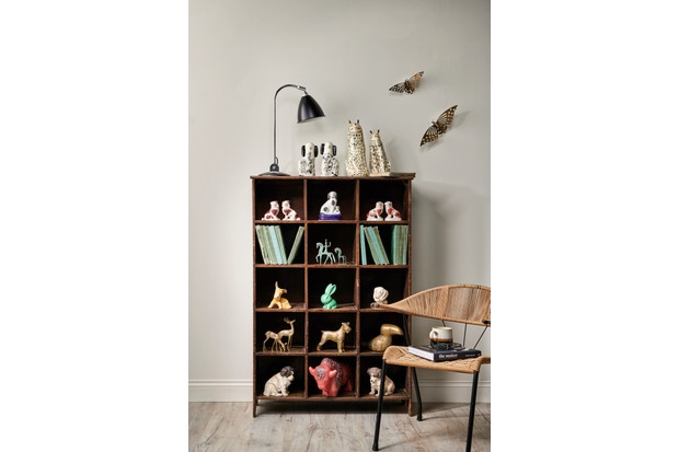 A colour co-ordinated display of miniatures in a pigeon hole unit with a Gubi lamp, vintage brass butterflies