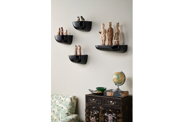 Ancient ornaments displayed on wall-mounted shelves. Modernist cornice shelves. Fragile ancient figures