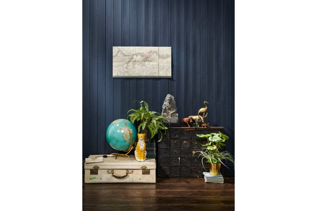 Tribal and oriental themed display of ornaments including vintage brass animals, ancient stone buddhas and plants