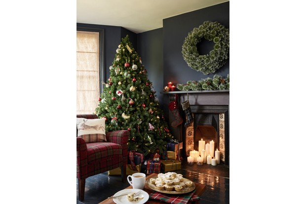 A large green Christmas tree stands next to a fireplace lit with pillar candles. Red and gold decorations fill the tree. Layered with traditional tartan this classic look oozes comfort and class
