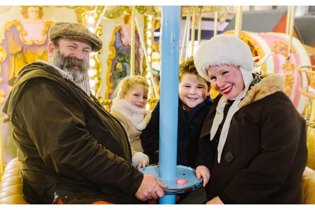Dick and Angel Strawbridge, plus their children, dressed for winter on an old-fashioned fairground ride