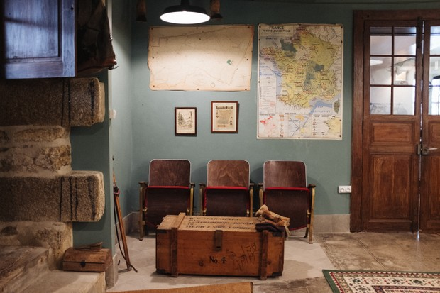 The Boot Room at Chateau de la Motte Husson - painted sage green with a row of vintage cinema seats and an antique chest