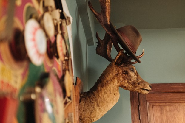 A taxidermy stags head is mounted on the wall in the Boot Room at the Chateau de la Motte Husson
