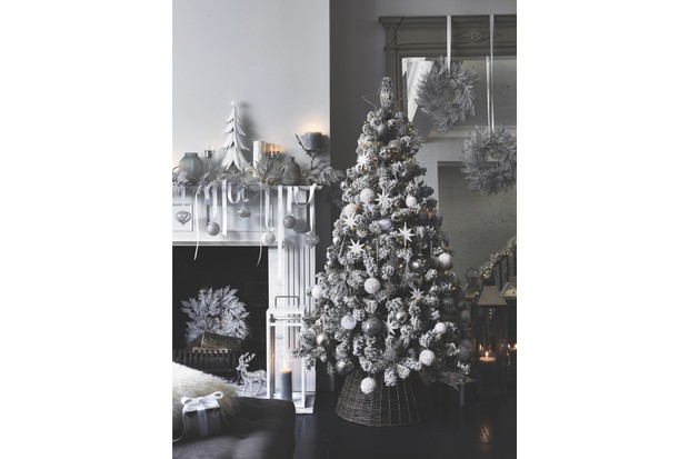 A white and silver hued tree sparkles next to a white fireplace with various white and silver decorations
