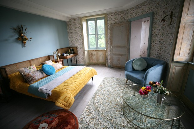 The Potagerie Suite in Chateau de la Motte Husson - a large room decorated in floral wallpaper with a wooden bed covered in a yellow bedspread