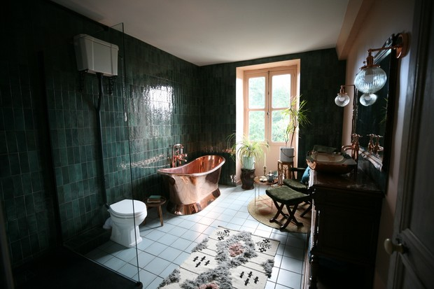 The Potagerie Suite bathroom at Chateau de la Motte Husson - walls are painted dark green and bold copper bathtub sits in the centre of the room