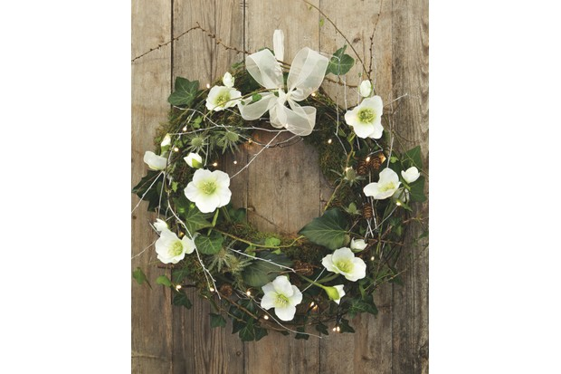 Homemade Christmas wreath with fresh flowers, foraged greenery and white bow