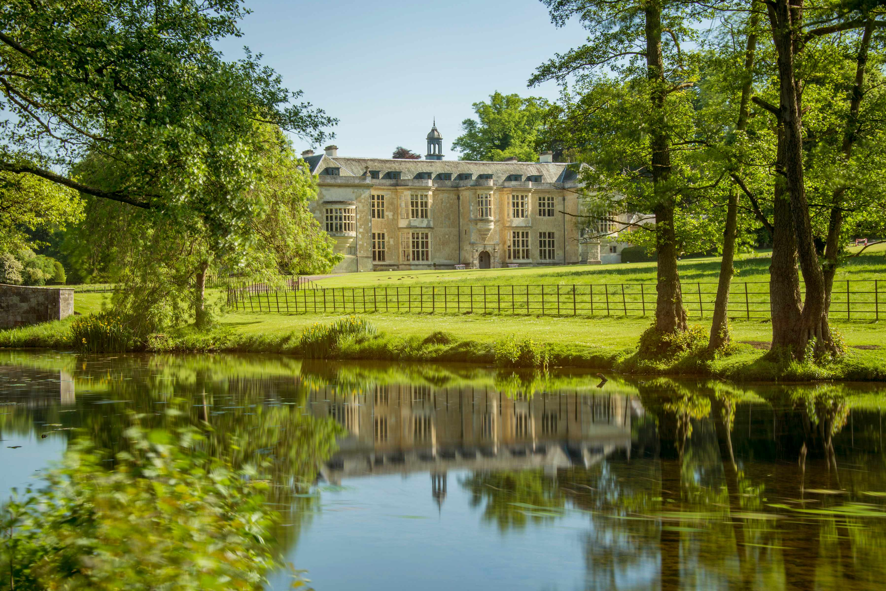 A view of Hartwell House on a sunny day across the river