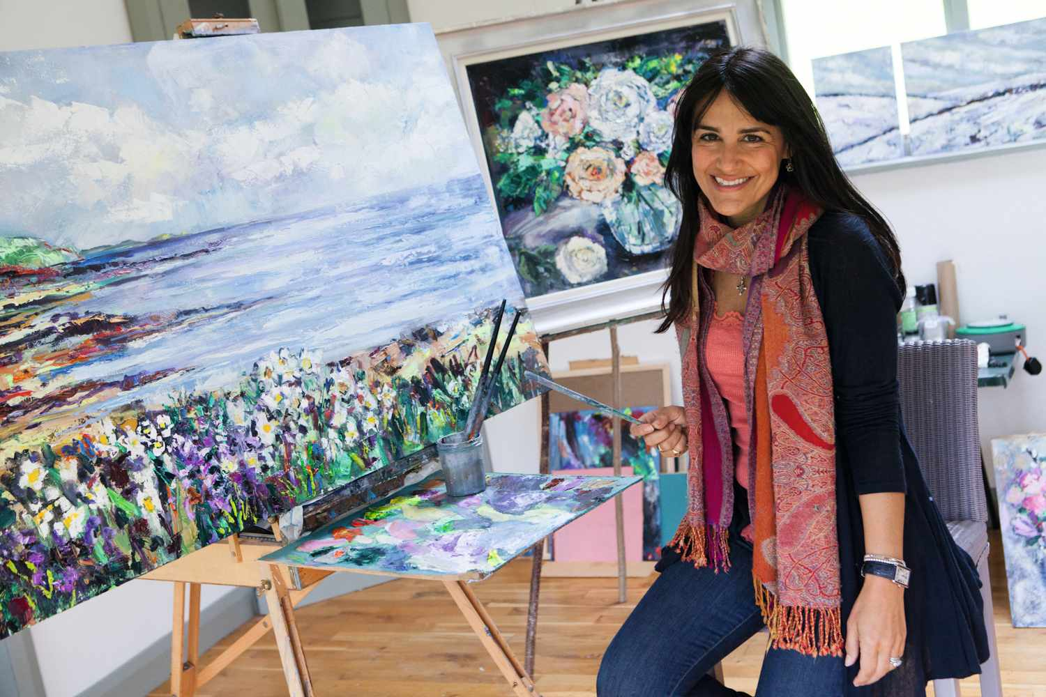 Artist Laura Wallace surrounded by oil paintings