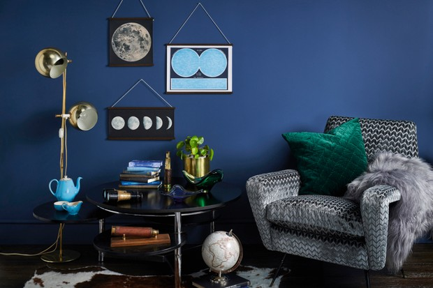 An elegant living room or cosy snug decorated with pieces inspired by the stars. Dark, moody walls mirror a clear night sky and make for a potent backdrop