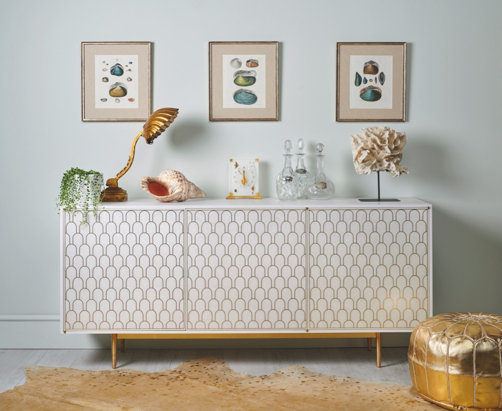 A chic white and gold cabinet displayed alongside a variety of antique collectables including shell prints, scallop gilt lamp, antique coral and gold leather pouffe