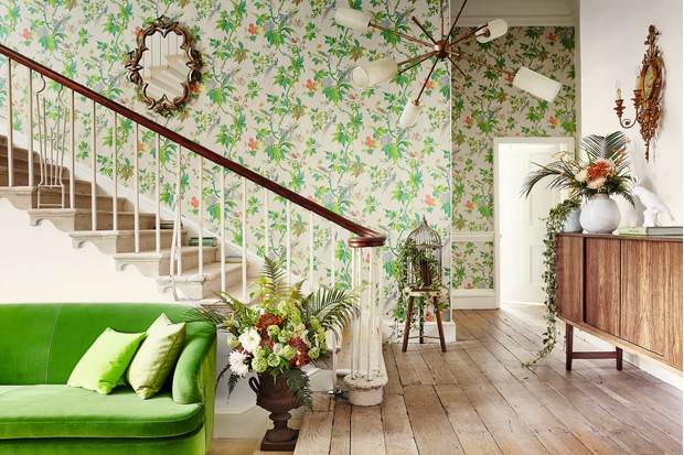 Little Greene Paradise Feather wallpaper paired with reclaimed floorboards, vintage lighting and antique pieces. Vases and planters are filled with flowers and foliage