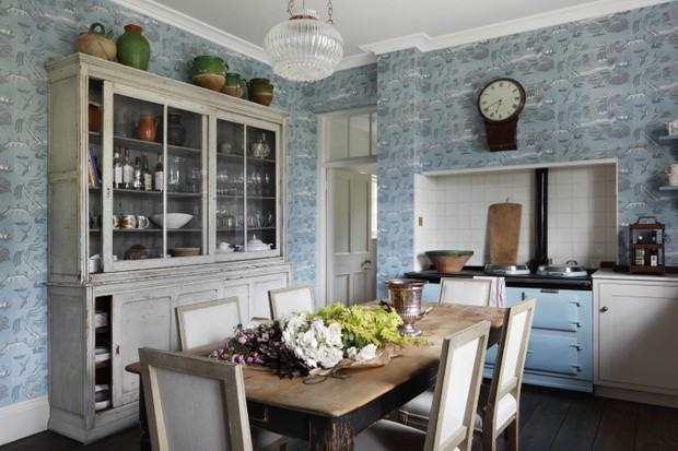 A homely VSP Interiors Devon kitchen filled with an antique wall clock, rustic table, French confit pots and a pale blue Aga