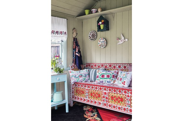 A floral Transylvanian bench used as storage for shoes and other homewares. Embroidered cushions line the bench and ceramic plates are mounted on the wall