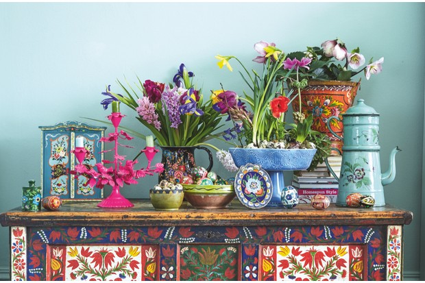 A vibrant Easter display of painted eggs, antique and vintage ceramics on a hand-painted folk art marriage chest