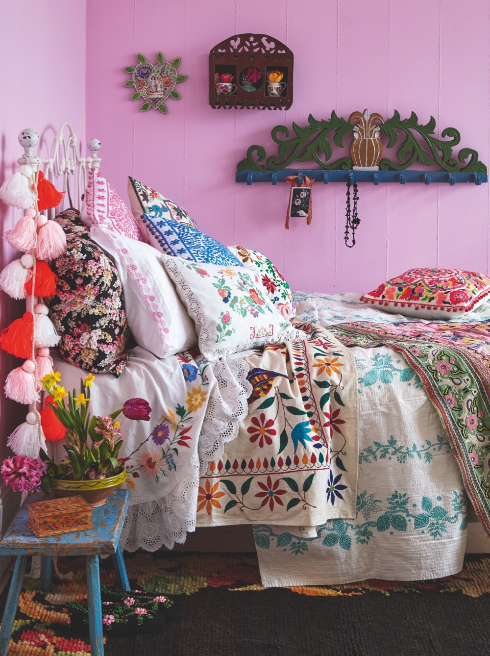 A folk-style bedroom layered with antique and vintage quilts and throws