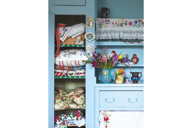 A linen cupboard arranged with a collection of vintage eiderdown