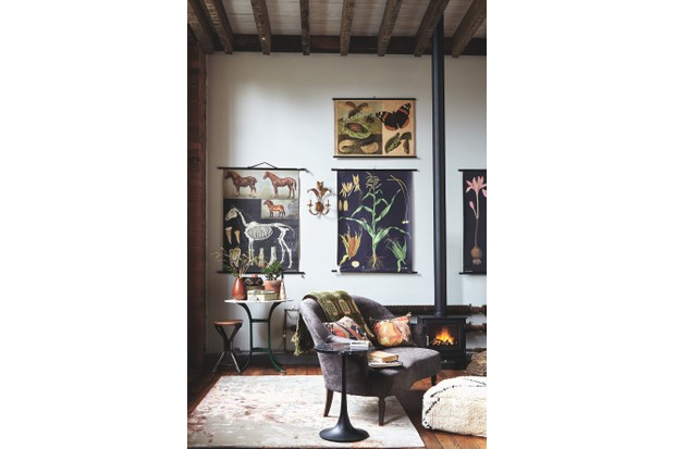 Vintage wall charts hang in a living room setting with various vintage pieces including a gilt wall sconce, table, stool and a log burner.