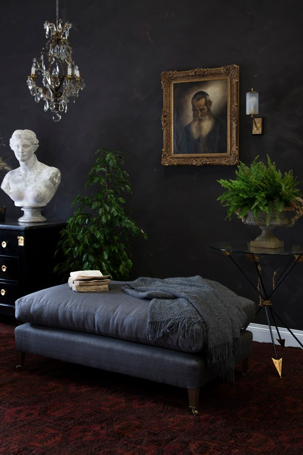 A black ottoman and classical antiquities sit against a chalky, black wall