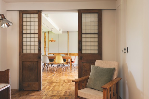 Salvaged sliding doors leading to a dining room that includes vintage DSW chairs in yellow, orange and green