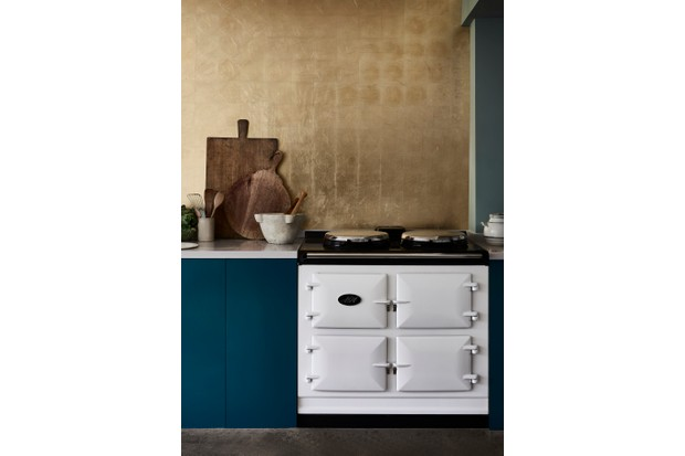 A white AGA alongside dark blue kitchen cupboards and a gilded splash back