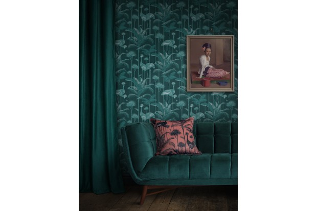 A rich, emerald velvet sofa against dark green floral wallpaper