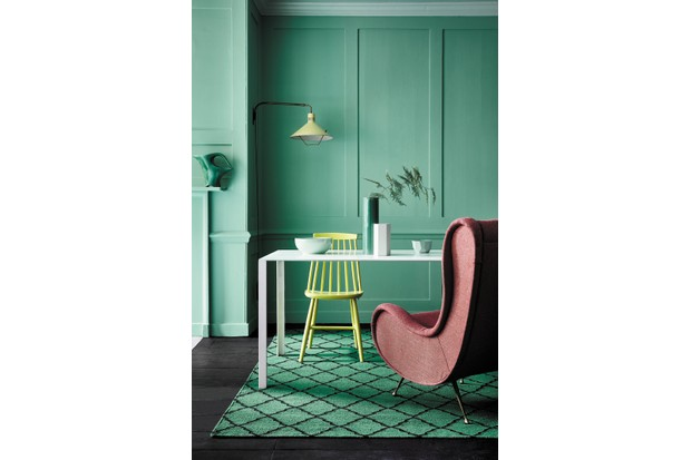 A blush pink mid-century armchair sits against bright green walls