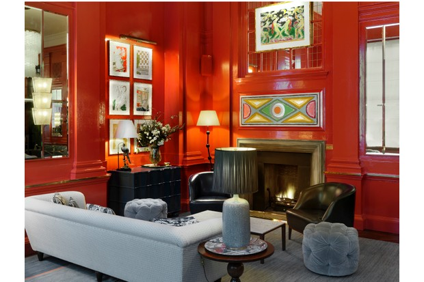 A sitting room with antique sofas and fireplace painted in bold, bright coral