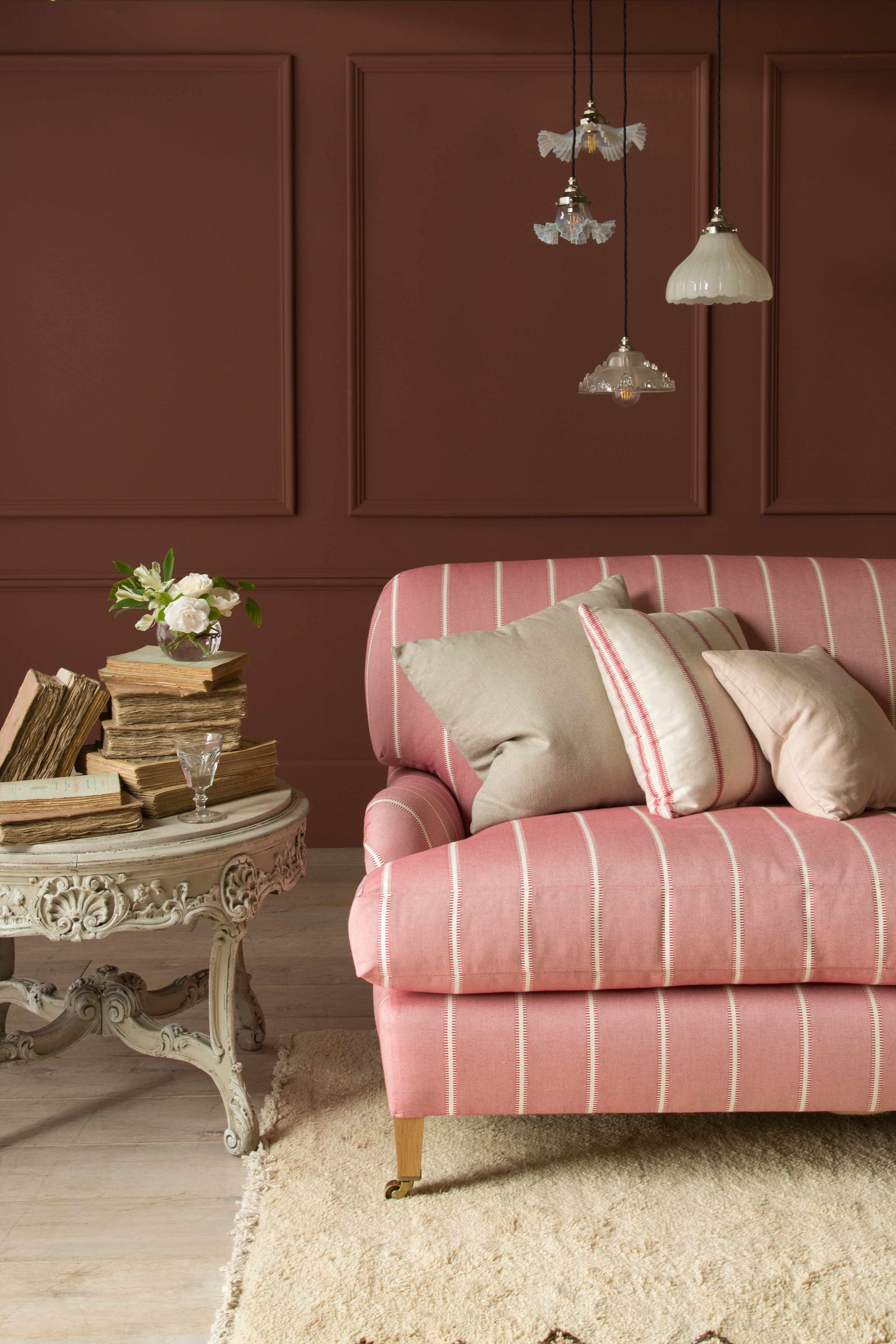 A coral striped sofa in front of a burgundy wall