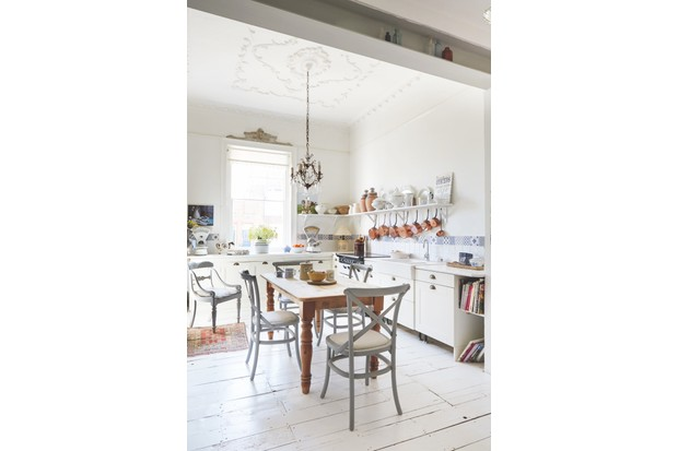 A light and bright country kitchen with antique copper pans and vintage ceramics